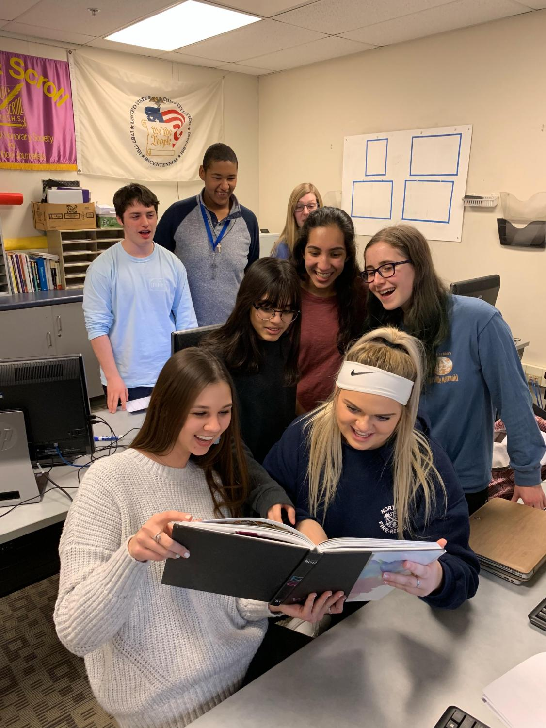 The yearbook staff huddles around a previous yearbook during their late night.