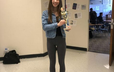 Kelly Bush, senior, holds a 1st place trophy. Bush who used to compete in Irish dance competitions, or feises, frequently won.