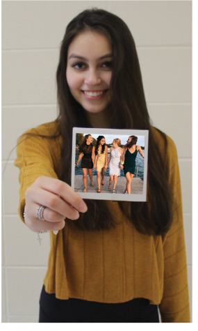 Chloe Faris, senior, holds an old polaroid out in front of her. Faris says she has had to make sacrifices in order to graduate early.