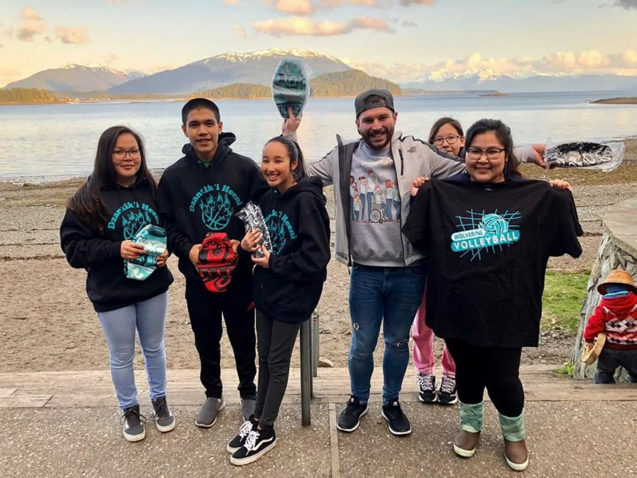 Jordan Addison, new English teacher, stands with his students in Alaska. His students wear their school spirit in form of t-shirts and hoodies as he supports the team.