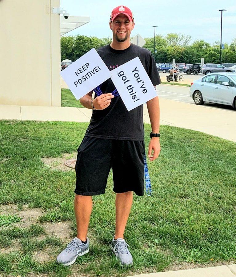 "Randal Dunbar, girls cross country and boys track and field coach, poses with two signs that resemble a positive mindset. ""If the players think positive, it leads to a positive experience overall, whether you're winning or losing,"" Dunbar said."