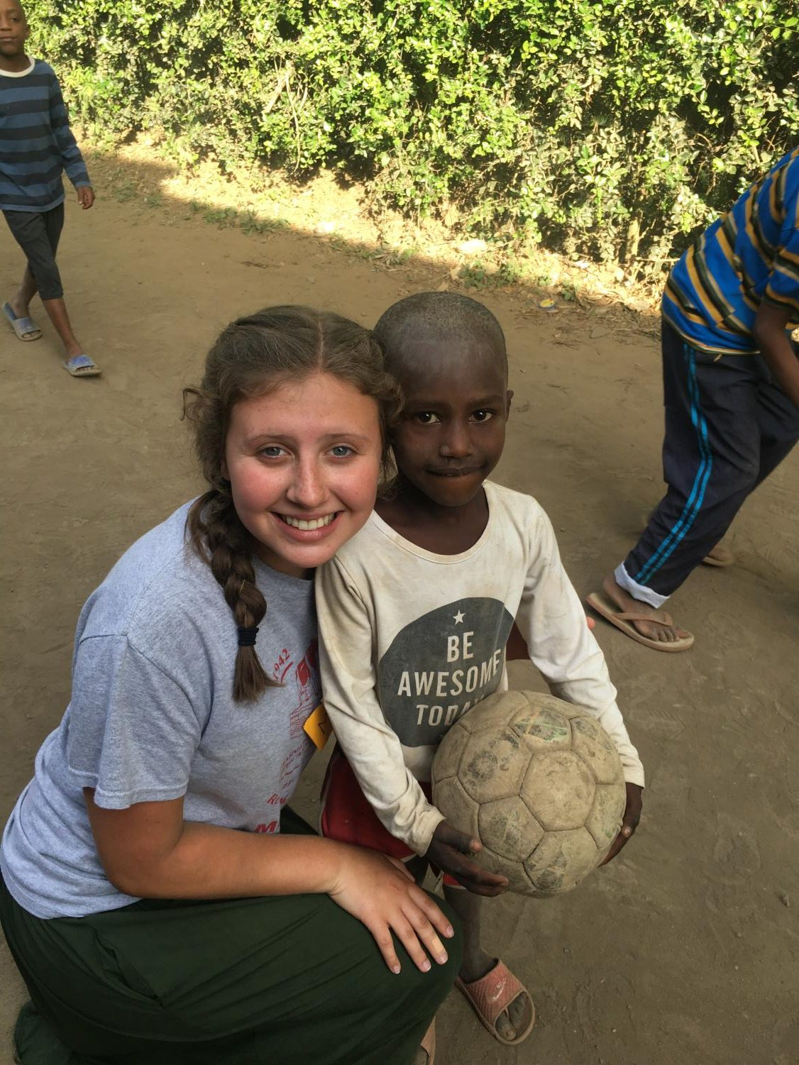 Maya Wiley, senior, smiles with one of the kids from Africa, after playing soccer. Wiley not only played with the kids, but she also helped improve their schools.