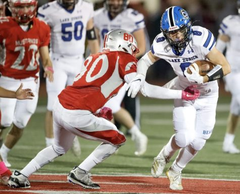 An LZ football player shields the ball against Mundelein at the game on October 18. Key touchdowns were made by Thomas Vages, Hunter Welcing, Collin Callahan, and Jack Moses.