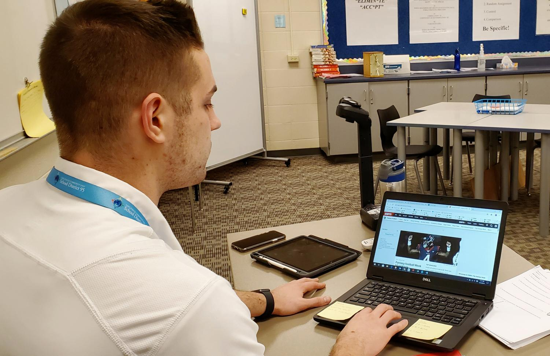 Timothy Beranek, math teacher, checks the fantasy football statistics during a free period.