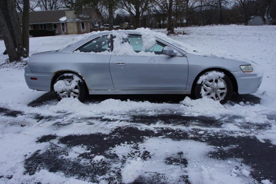 A snow-covered car sits in the middle of a driveway, waiting to be taken on a drive. With snow on the tires and on the roads, people need to give themselves extra time to slow to a stop.