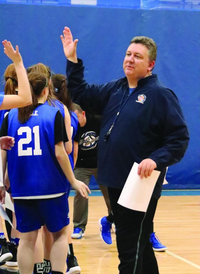 Christopher Bennett, girls basketball coach and economics teacher, gives a high five to one of his players after a practice. Bennett has been on the coaching staff for 22 years and has over 200 career wins.