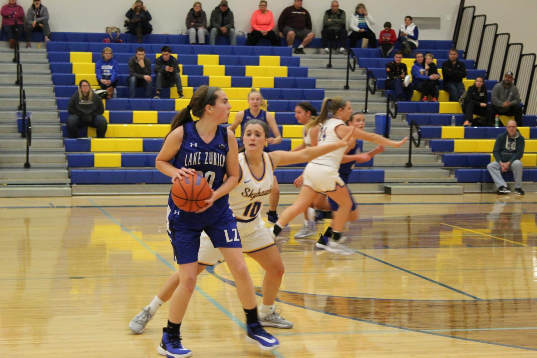 Baylie Parks, member of the girls varsity basketball team, defending the ball.