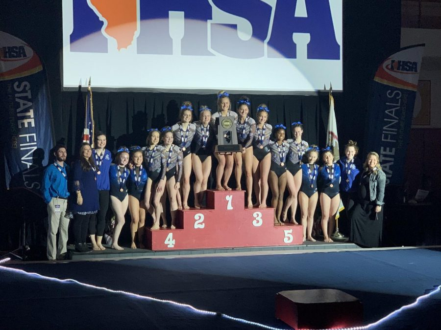 The gymnastics team poses with their trophy at State.