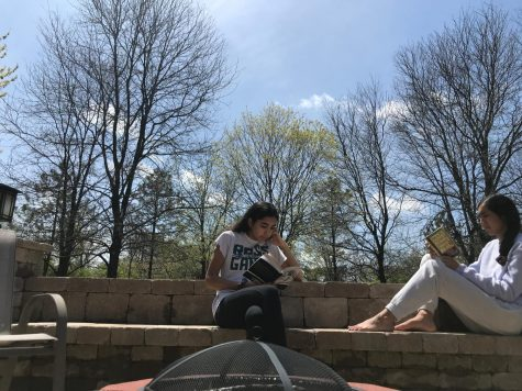 Zoya Hasan and Zara Hasan sit outside and read after a day of e-learning.