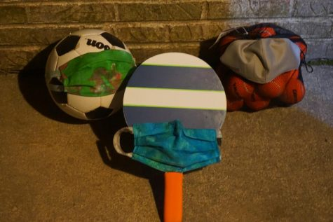 A soccer ball, ping-pong paddle, and a bag of tennis balls lay on the ground. This equipment cannot be used for PE classes due to curriculum changing to low-intensity workouts and mindfulness.