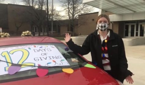 Ashley DeLuga, junior Student Council Executive Officer, explains the car decoration contest occuring during the 12 Days of Giving, which students can participate while  dropping off their donations at school.