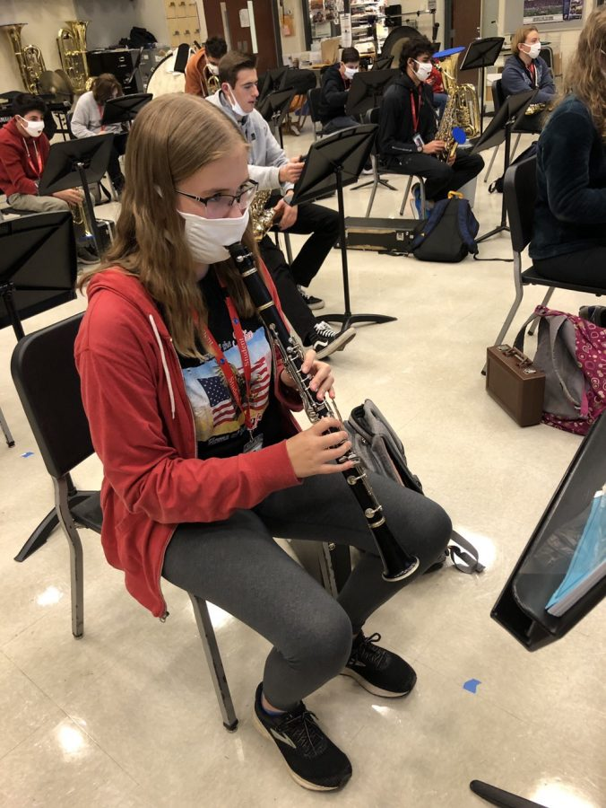 "Grace Trumbull, junior hybrid learner, plays her clarinet in band by having a hole through her mask. Trumbull says her choice to return back to school was influenced ""mainly because of choir and band. Singing and playing an instrument have been a disappointment during e-learning because I have to practice by myself."""
