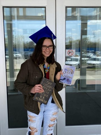"""Bella Brunke, senior, holds up two of her favorite books, """"The Invisible Life of Addie Larue"""" and """"The Queen of Nothing"""""""