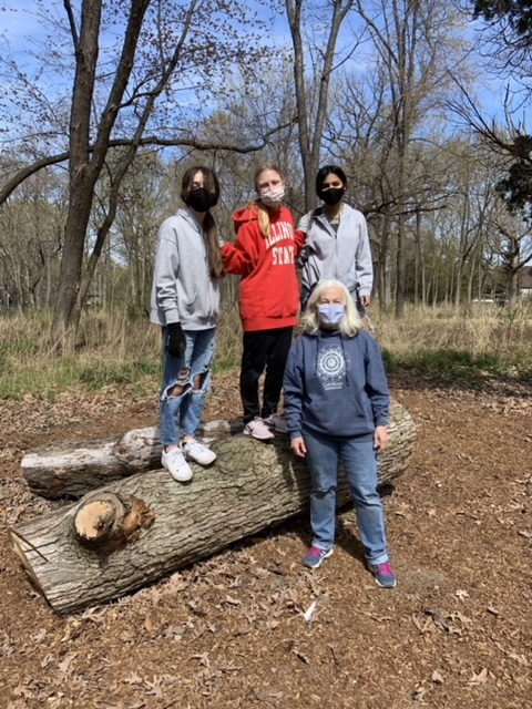 Members of the REACT club smile as they work on helping the forests in Lake Zurich. They remove an invasive species from the oak trees surrounding LZHS.
