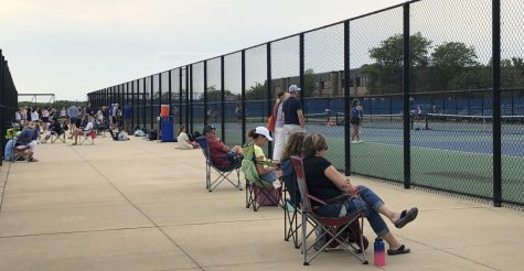 Family members of tennis players sit beside the courts to cheer on their children.