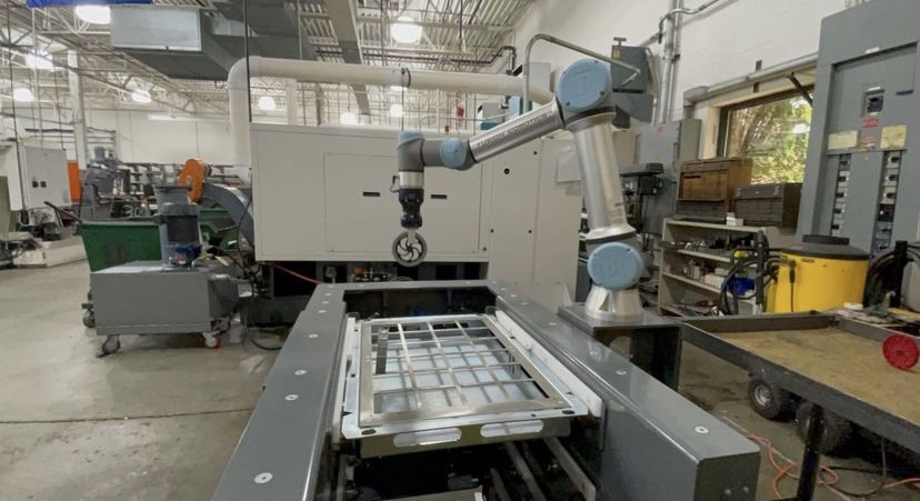 At 18 Manufacturing, Anand works with a robotic arm to further his engineering experience
